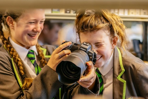 Two girls, one looking through camera lens